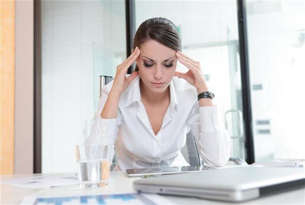 Overworking business woman suffering from headache in office