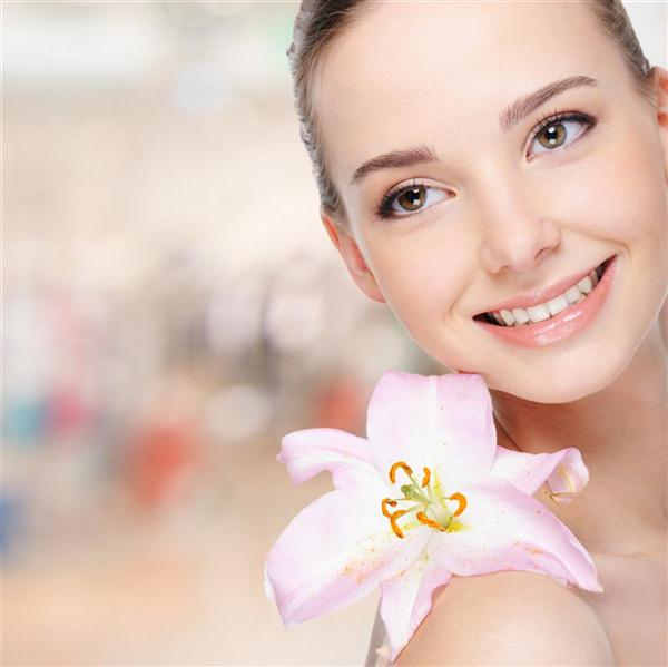 Beautiful happy young woman with lily on body at face
