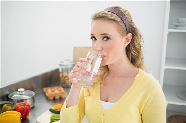 Content cute blonde drinking a glass of water in bright kitchen