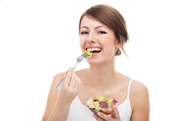 Woman eat salad on diet. Smiling. Healthy food. Isolated on white